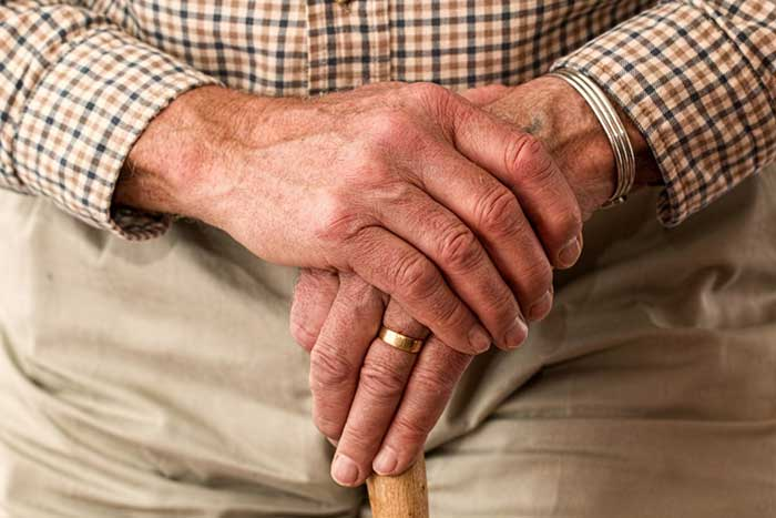 elderly person hands with a cane